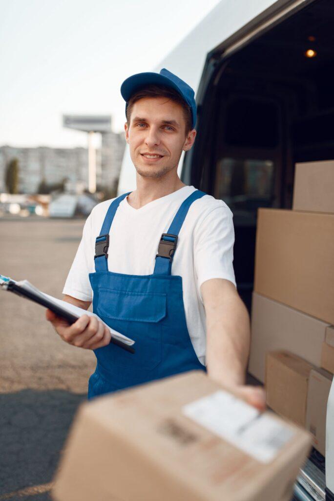 deliveryman-in-uniform-gives-parcel-delivery-NLBP7VP-1
