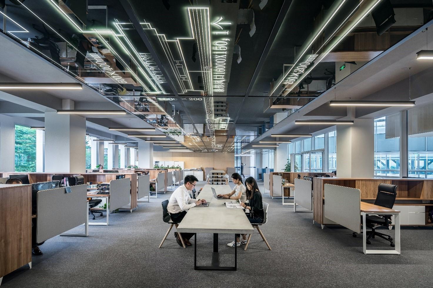 ufficio open space con grande scrivania centrale e tre persone che lavorano