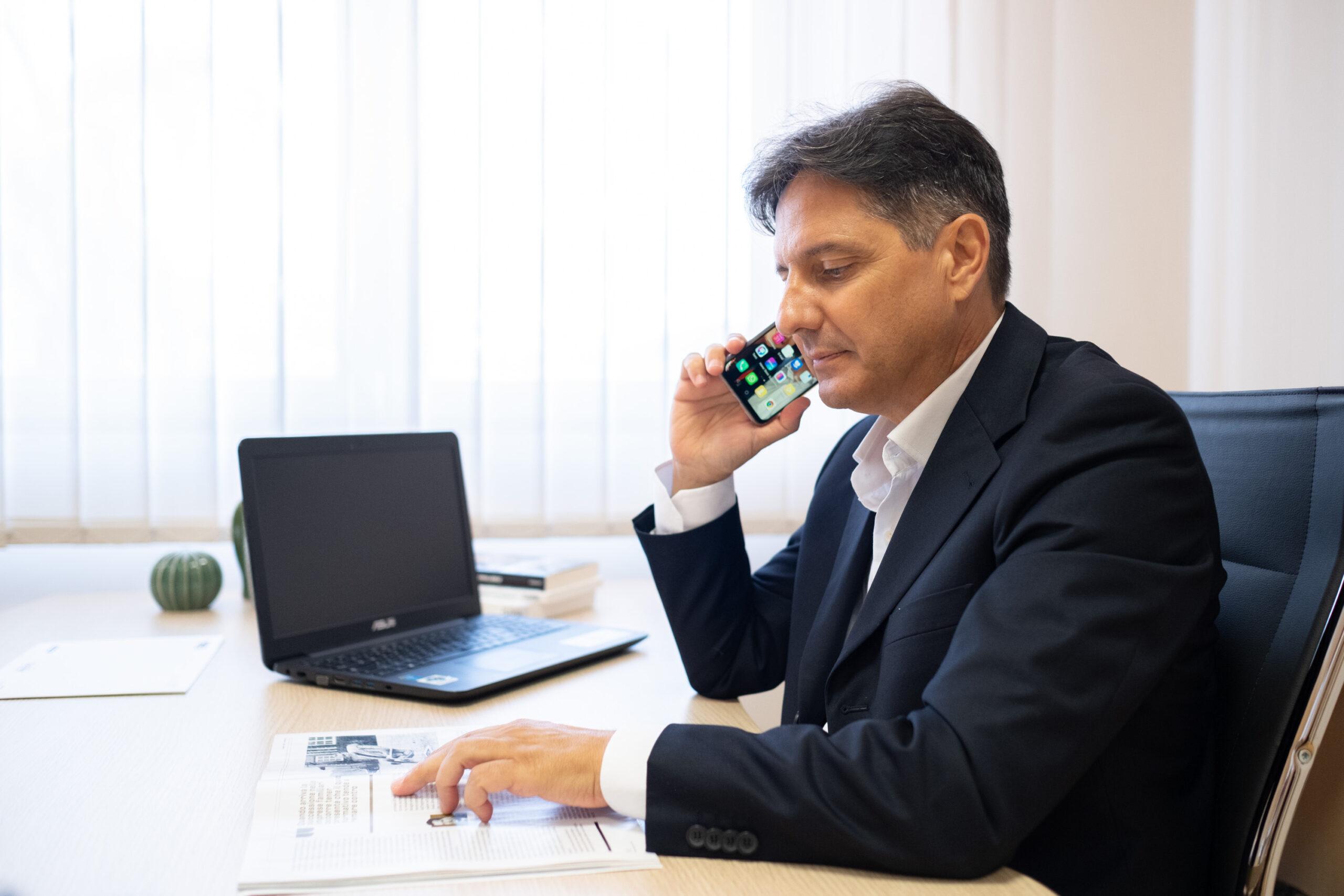 business man al telefono seduto alla scrivania nel suo ufficio al Majestic