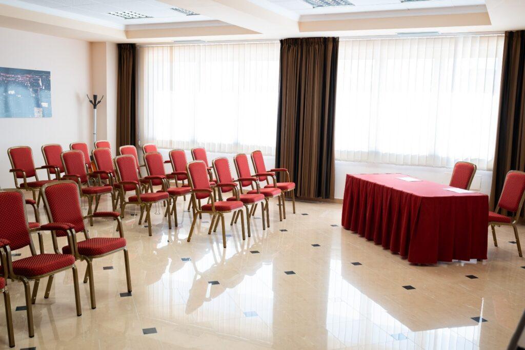 poltroncine e tavolo relatori nella sala conferenze del Majestic